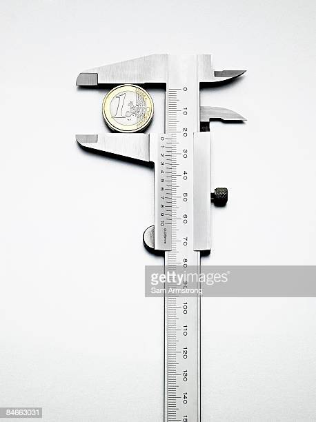 Euro coin measured by calipers.
