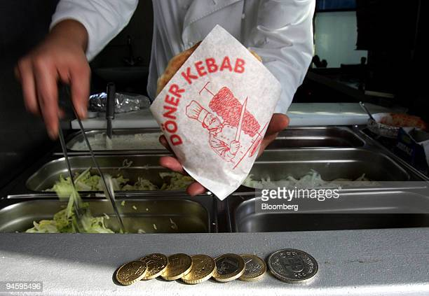 Euro coins and a five Swiss franc piece sit as payment at Kuecuek Coekelekci's kebab stand on the GermanSwiss border in Jestetten Germany on Thursday...