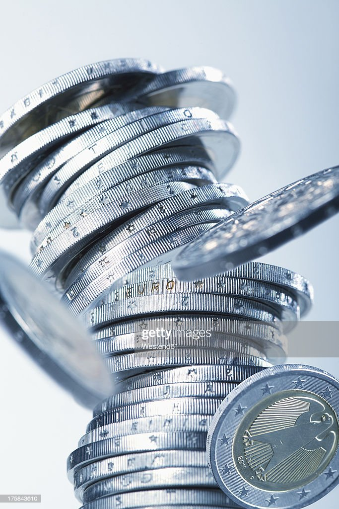 Euro coins collapsing against white background, close up : Stock Photo