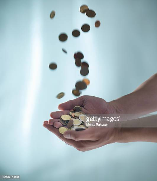 Euro coins falling into man's cupped hands