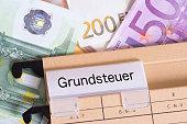 Euro Geldscheine und ein Hängeordner mit den Unterlagen für die Grundsteuer