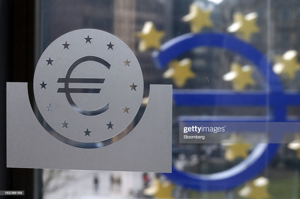 A euro logo, left, sits etched into a glass pane inside the European Central Bank's (ECB) headquarters in Frankfurt, Germany, on Thursday, March 7, 2013. Draghi stuck to his view that the euro-area economy will gradually recover later this year as policy makers trimmed their economic and inflation forecasts. Photographer: Ralph Orlowski/Bloomberg via Getty Images