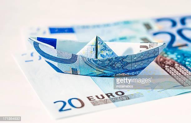 Euro paper boat standing on bills