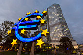 A euro sign sculpture stands illuminated in front of the European Central Bank headquarters in Frankfurt Germany on Thursday Oct 23 2014 At noon in...