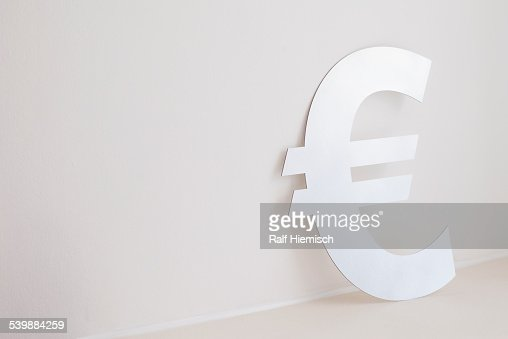 Euro symbol against wall