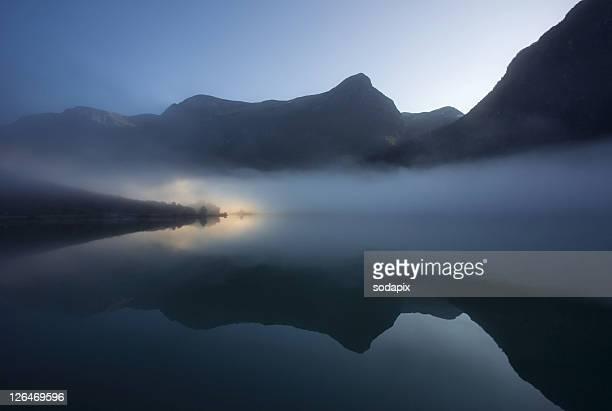 Europa, Skandinavien, Norwegen, Stryn, Olden, Oldevatn, Aufgehende Sonne beleuchtet Landzung des Sees an einem nebligen Morgen