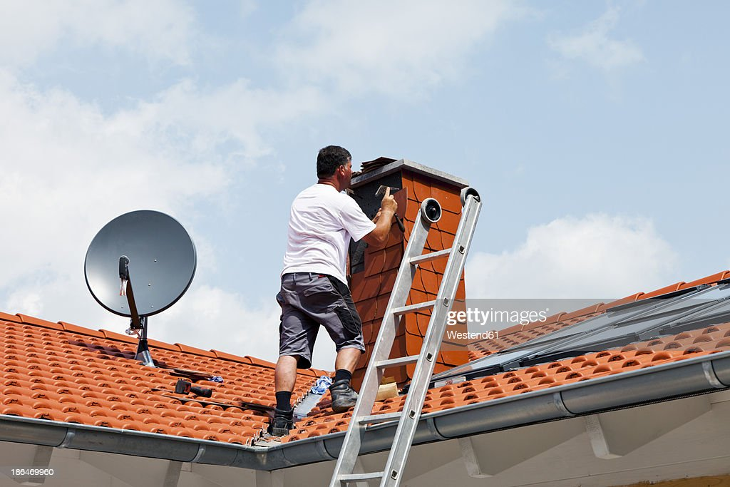 Europe, Germany, Rhineland Palatinate, Man covering chimney with roofing shingles