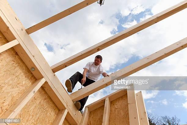 Europe, Germany, Rhineland Palatinate, Man standing on roof beam