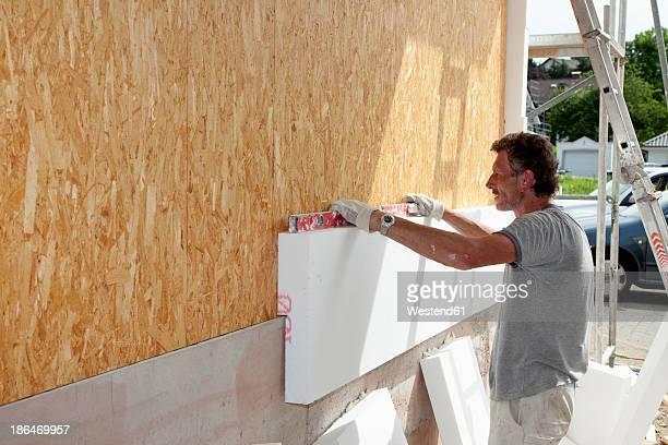 Europe, Germany, Rhineland Palatinate, Man sticking polystyrene on wooden house wall