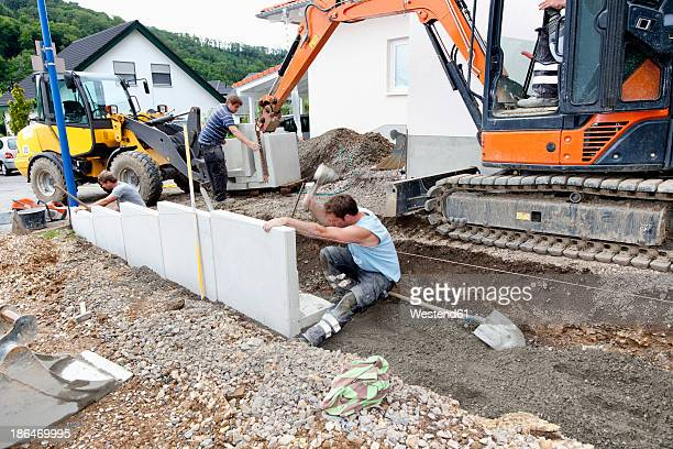 Europe, Germany, Rhineland Palatinate, Men installing corner stone in soil while house building