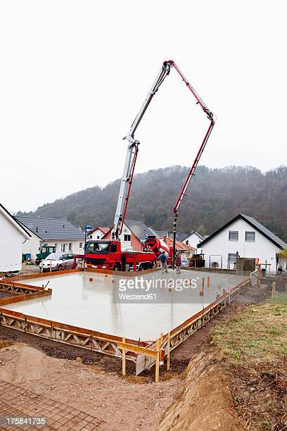 Europe, Germany, Rhineland-Palatinate, Construction workers filling concrete in casing for foundation