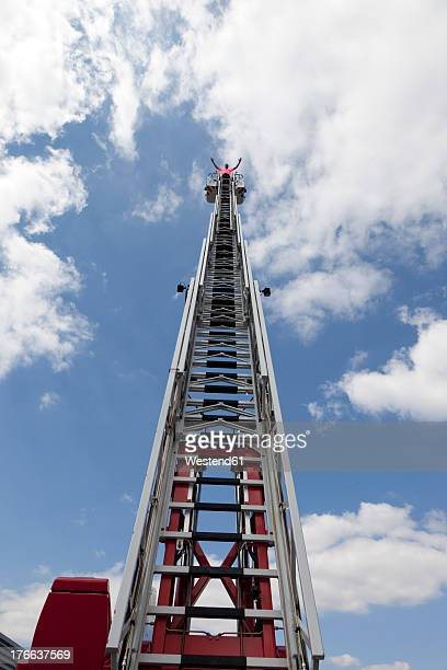 Europe, Germany, Rhineland-Palatinate, Man standing on top of fire engine ladder
