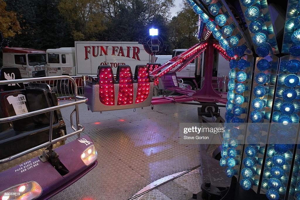 Europe, Great Britain, England, London, Victoria Park, fairground ride at dusk, parked vans in background