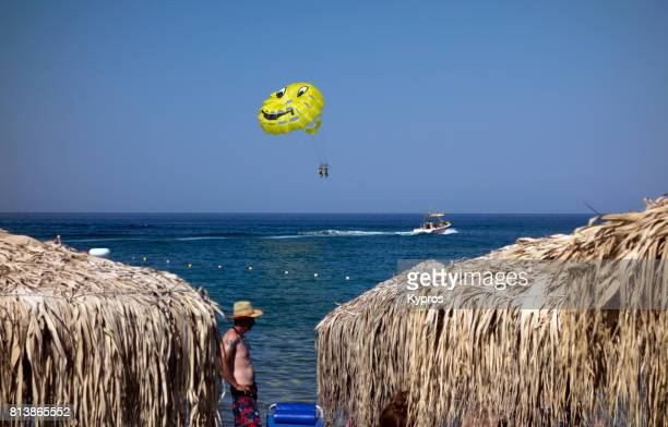 Europe, Greece, Rhodes Island, Faliraki Area, View Of Man Wearing Straw Hat And Trunks Standing On Beach. Watersports With Yellow Parasail And Speedboat (Background)