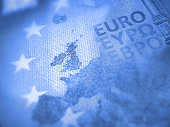 Unfocused Euro bill close up detail of Europe map with focus on Great Britain. Brexit concept in blue color
