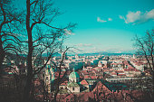Photo depicting a view from the Castle hill to the downtown city of Ljubljana, Slovenia. Austrian Alpine Mountains on the background.