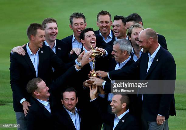 Europe team captain Paul McGinley and Rory McIlroy of Europe pose with the Ryder Cup trophy and team mates after the Singles Matches of the 2014...