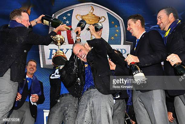 Europe team captain Paul McGinley lifts the Ryder Cup trophy as he is sprayed with champagne by Jamie Donaldson of Europe after the Singles Matches...