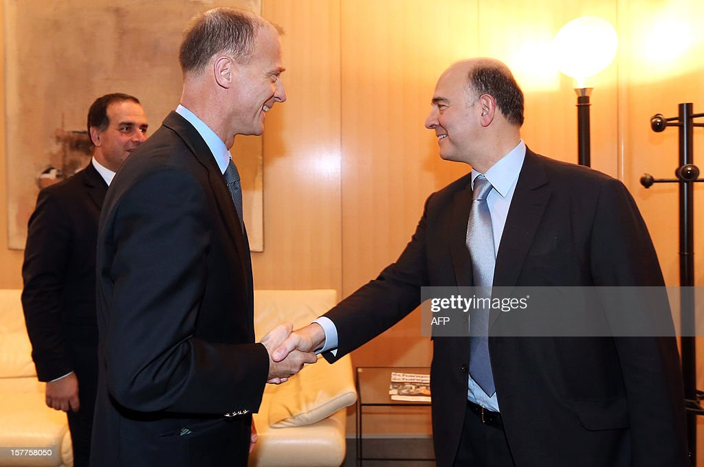 European Aeronautic Defence and Space company (EADS) German CEO Tom Enders (C) shakes hands with French Minister of Economy, Finance and Foreign Trade Pierre Moscovici (R) next to French director for strategy at EADS Marwan Lahoud (L) on December 6, 2012 in Paris. Lahoud, described the company's share restructuring announced late on December 5, which ends the ability of the French and German governments effectively to control the group, as a 'new birth.'