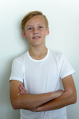 European boy smiling and standing against white background
