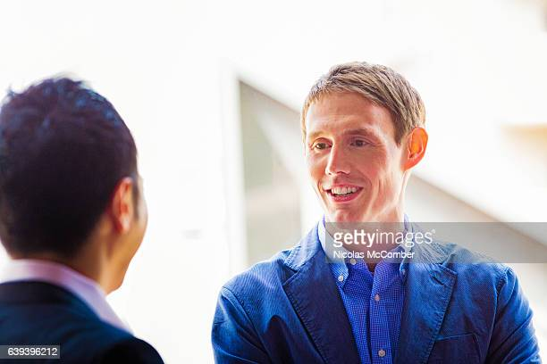 European businessman smiles as he is greeted by Asian colleague