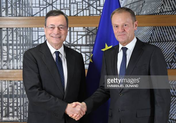 European Central Bank President Mario Draghi is welcomed by European Union President Donald Tusk at the European Council in Brussels on December 4...
