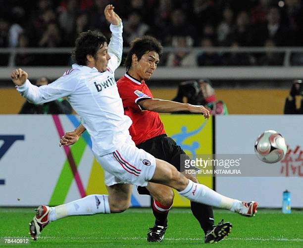 European champion AC Milan defender Massimo Oddo attempts to block Asian champion Urawa Reds midfielder Takahito Soma during their Club World Cup...