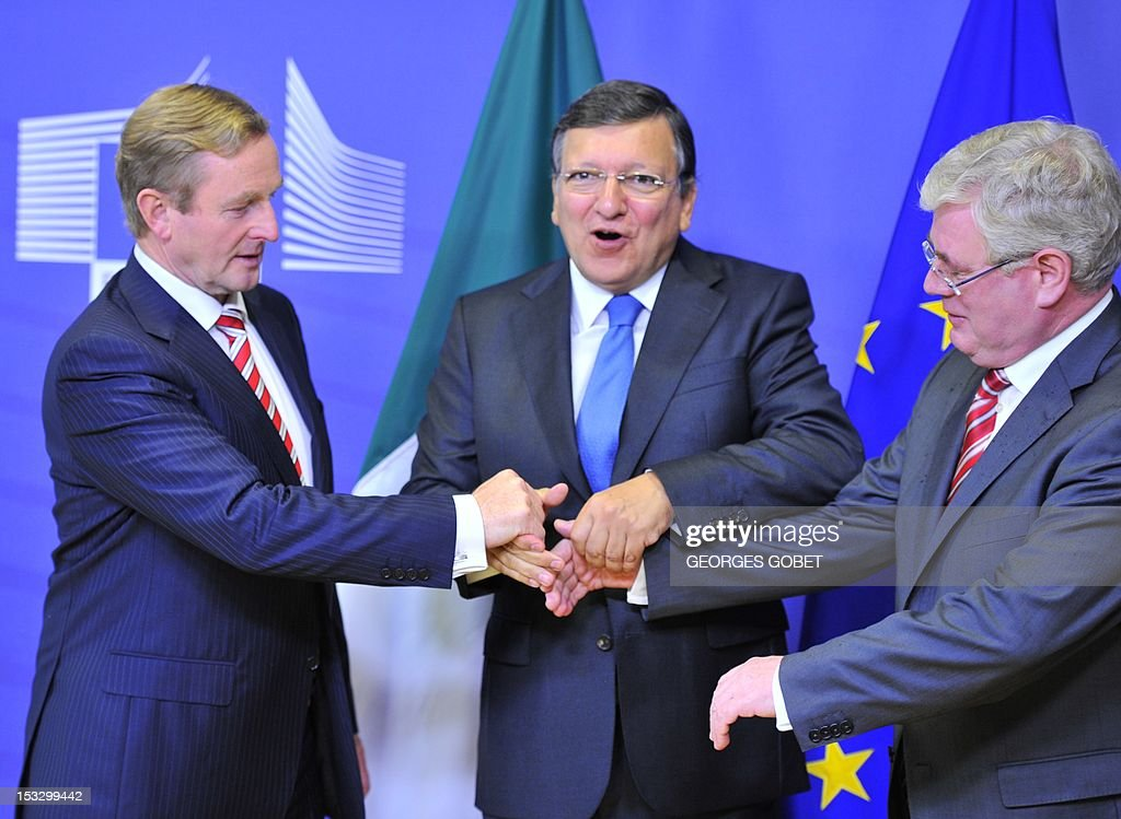 European Commission Chairman Jose Manuel Barroso (C) welcomes Irish Prime Minister Enda Kenny (L) and Deputy Prime Minister Eamon Gilmore on October 3, 2012 before a working session at EU Headquarters in Brussels. Ireland will take over the EU's six-month rotating presidency on January 1, 2013. AFP PHOTO / GEORGES GOBET