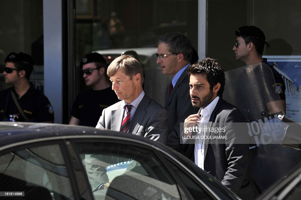 European Commission director Matthias Morse (L) and European Central Bank's (ECB) Mission Chief for Greece Klaus Masuch (back-C) leave the Greek ministry of finance under police protection as a group of protesters gather nearby in Athens on September 26, 2013. Auditors from Greece's 'troika' of creditors -- the EU, IMF and European Central Bank - are conducting a scheduled inspection of progress on pledged structural reforms. Under obligations taken in return for EU-IMF loans, Greece has pledged to axe 4,000 state jobs and redeploy 25,000 public sector workers by the end of the year.
