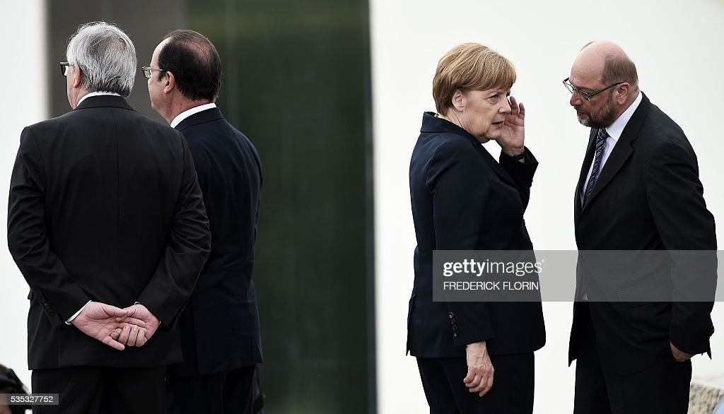 European Commission President Jean Claude Juncker, French President Francois Hollande, German Chancellor Angela Merkel and President of European Parliament Martin Schulz talk during a remembrance ceremony to mark the centenary of the battle of Verdun, at the Douaumont Ossuary (Ossuaire de Douaumont), northeastern France, on May 29, 2016. The battle of Verdun, in 1916, was one of the bloodiest episodes of World War I. The offensive which lasted 300 days claimed more than 300,000 lives. / AFP / FREDERICK