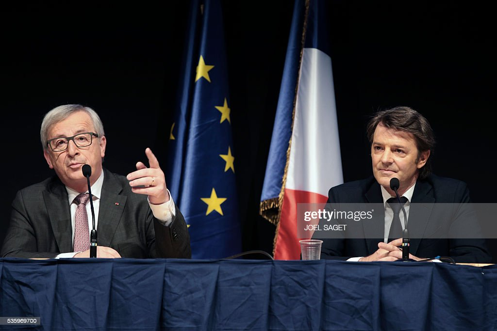 European Commission President Jean Claude Juncker (L) speaks as Association of the Mayors of France (AMF) president and Troyes mayor Francois Baroin listens on May 31, 201 at the Parc des expositions in Paris during the opening of the 99th France's Mayors congress. / AFP / JOEL
