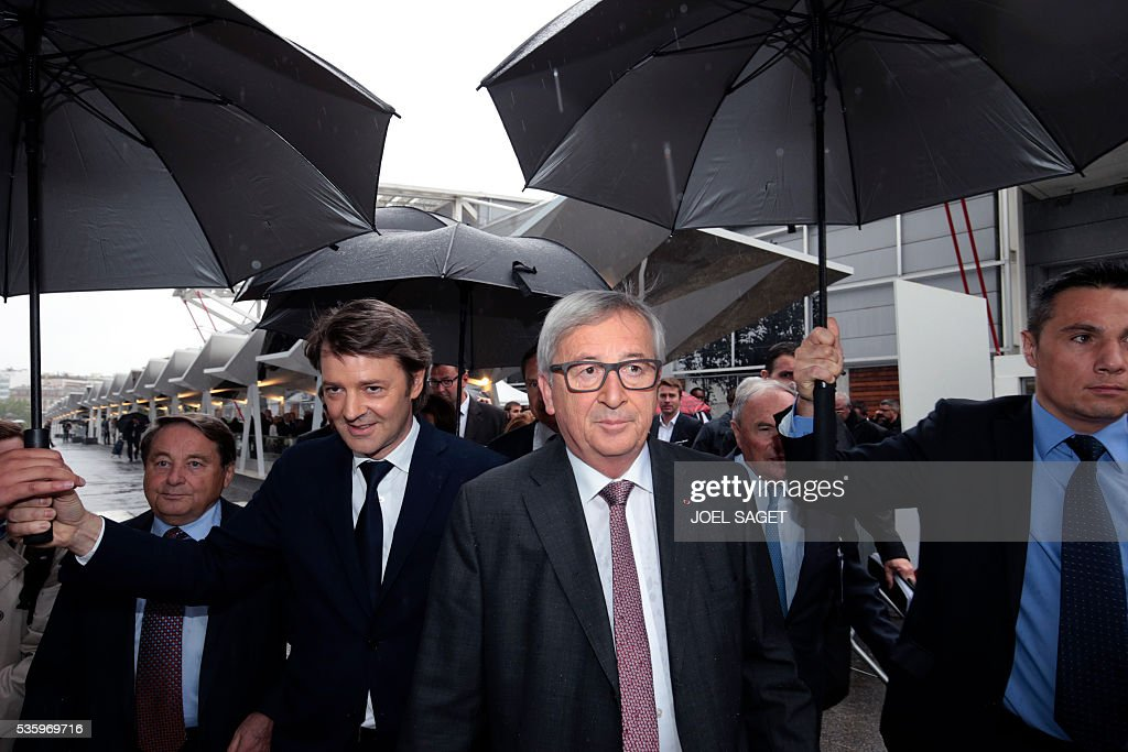 European Commission President Jean-Claude Juncker (C) and Association of the Mayors of France (AMF) president and Troyes mayor Francois Baroin (2L) arrive on May 31, 201 at the Parc des expositions in Paris during the opening of the 99th France's Mayors congress. / AFP / JOEL
