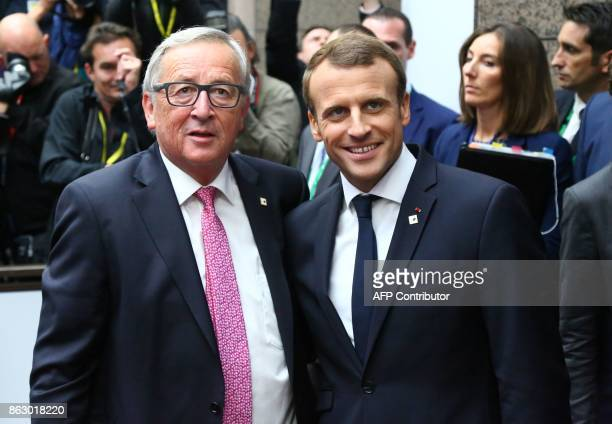 European Commission President JeanClaude Juncker and France's President Emmanuel Macron pose for photographs as they arrive in Brussels on October 19...