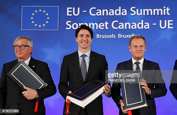 TOPSHOT European Commission President JeanClaude Juncker Canadian Prime Minister Justin Trudeau and European Council President Donald Tusk pose after...