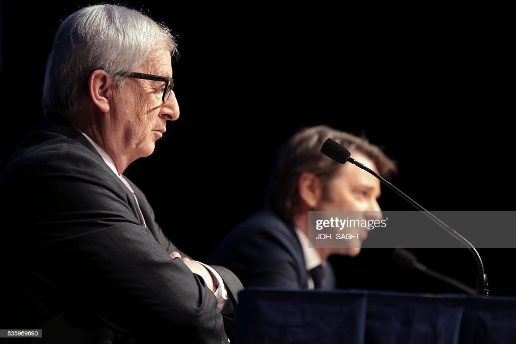 European Commission President Jean-Claude Juncker (L) listens as Association of the Mayors of France (AMF) president and Troyes mayor Francois Baroin speaks on May 31, 201at the Parc des expositions in Paris during the opening of the 99th France's Mayors congress. / AFP / JOEL