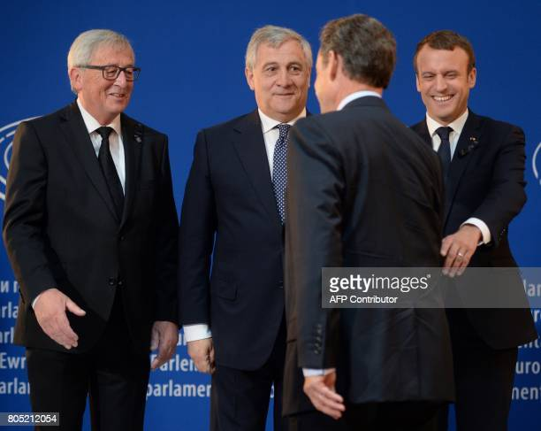 European Commission President JeanClaude Juncker President of the European Parliament Antonio Tajani and French President Emmanuel Macron react as...