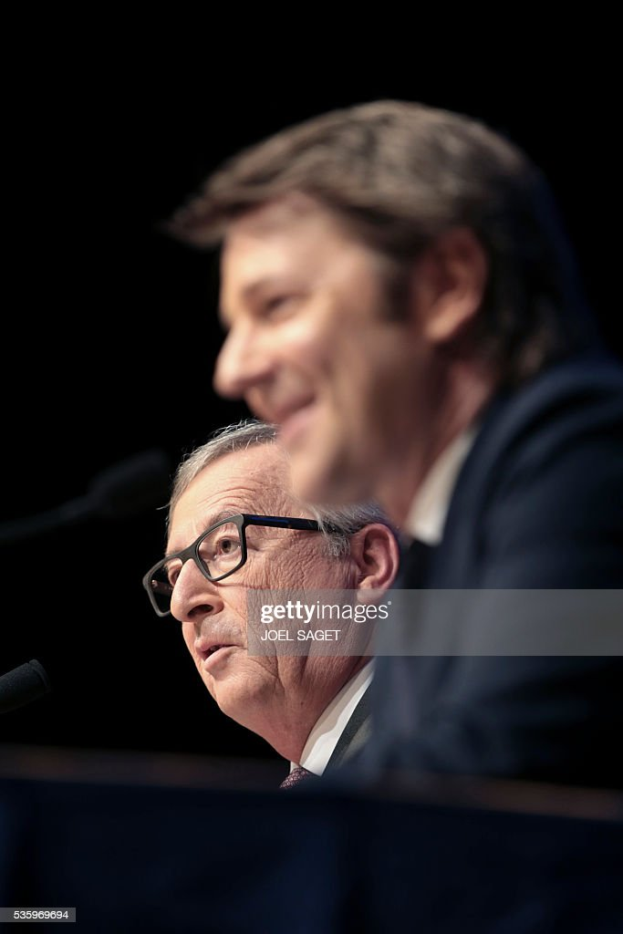 European Commission President Jean-Claude Juncker (L) speaks as Association of the Mayors of France (AMF) president and Troyes mayor Francois Baroin listens on May 31, 201at the Parc des expositions in Paris during the opening of the 99th France's Mayors congress. / AFP / JOEL