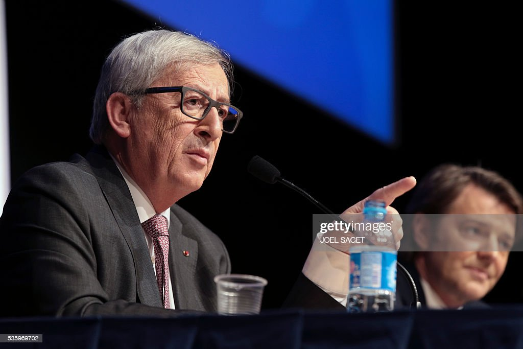 European Commission President Jean-Claude Juncker (L) speaks as Association of the Mayors of France (AMF) president and Troyes mayor Francois Baroin listens on May 31, 201 at the Parc des expositions in Paris during the opening of the 99th France's Mayors congress. / AFP / JOEL