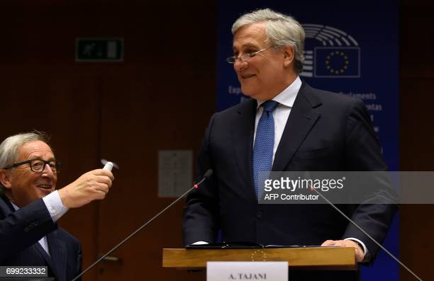 European Commission President JeanClaude Juncker uses a small ventilator next to European Parliament President Antonio Tajani before a High level...