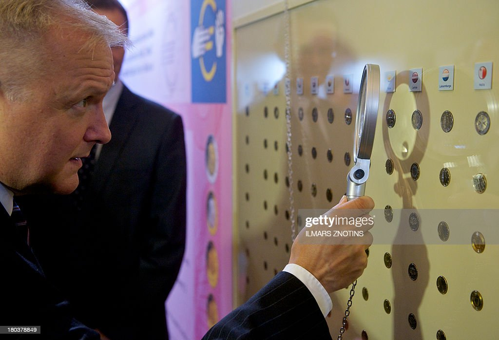 European Commission Vice President Oli Rehn looks at Latvian euro coin samples at a opening of the exhibition 'Euro-Our Currency' in Riga, Latvia, on September 12, 2013. Latvia replaces its current currency the lat with the euro in January 2012.