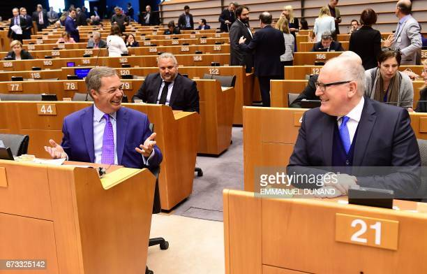 European Commission vicePresident Frans Timmermans talks with British Euroskeptic EU parliament member Nigel Farage during a planery session at the...
