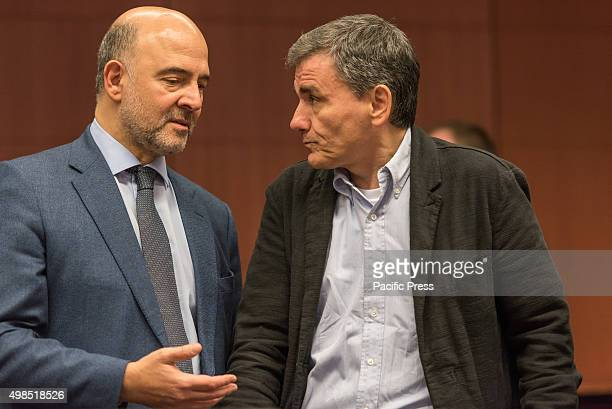 European Commissioner in charge of Economic and Financial Affairs Pierre Moscovici and Greek Finance Minister Euclid Tsakalotos speak to each other...