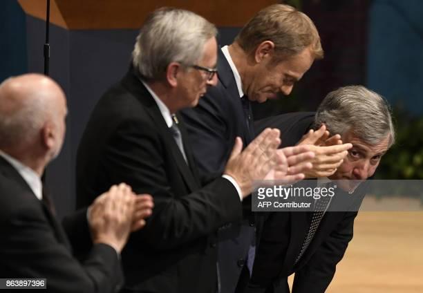 European Council president Donald Tusk and European Commission president Jean Claude Juncker applaud European Parliament president Antonio Tajani...