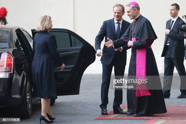 European Council President Donald Tusk and wife Malgorzata Tusk are welcomed by the prefect of the papal household Georg Gaenswein as they arrive at...