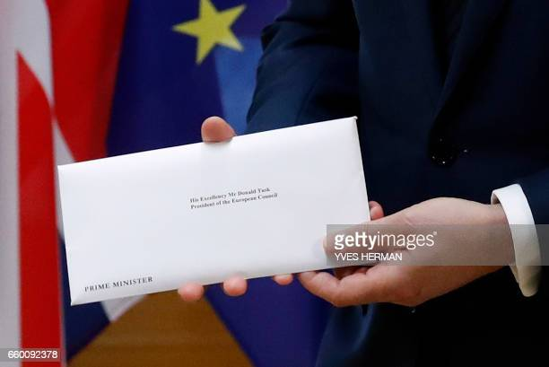 European Council President Donald Tusk holds British Prime Minister Theresa May's formal notice of the UK's intention to leave the bloc under Article...