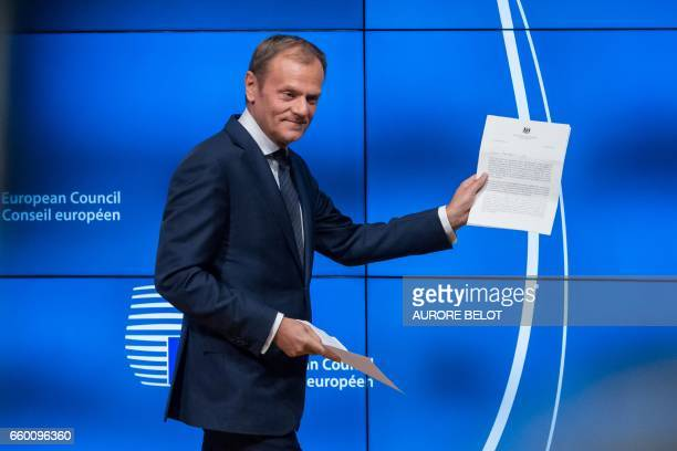 TOPSHOT European Council President Donald Tusk holds the formal notice launching the Brexit as he arrives to give a press conference in Brussels on...