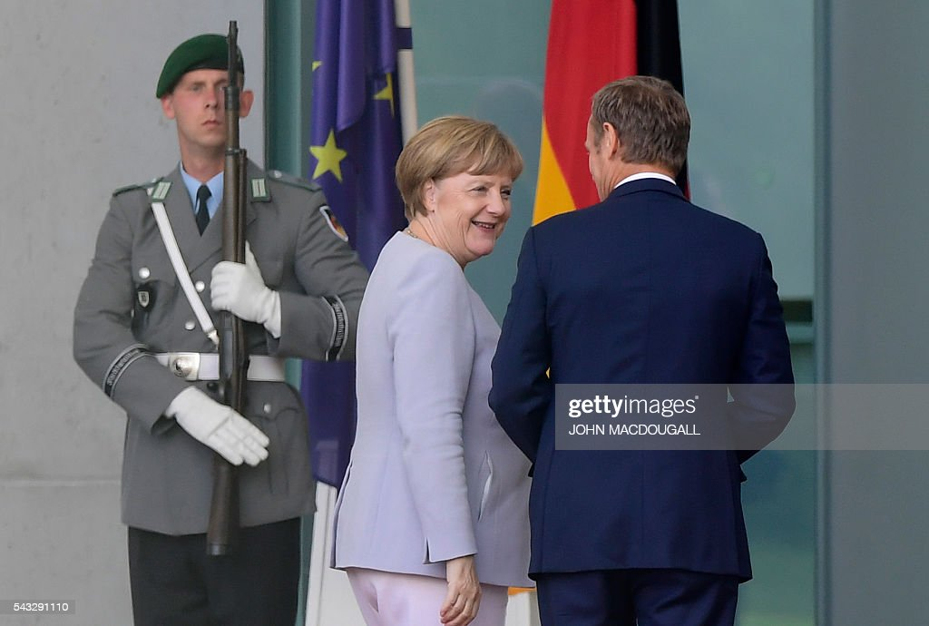 European Council president Donald Tusk (R) is welcomed by German chancellor Angela Merkel upon arrival for talks after the Brexit referendum at the chancellery in Berlin, on June 27, 2016. / AFP / John MACDOUGALL