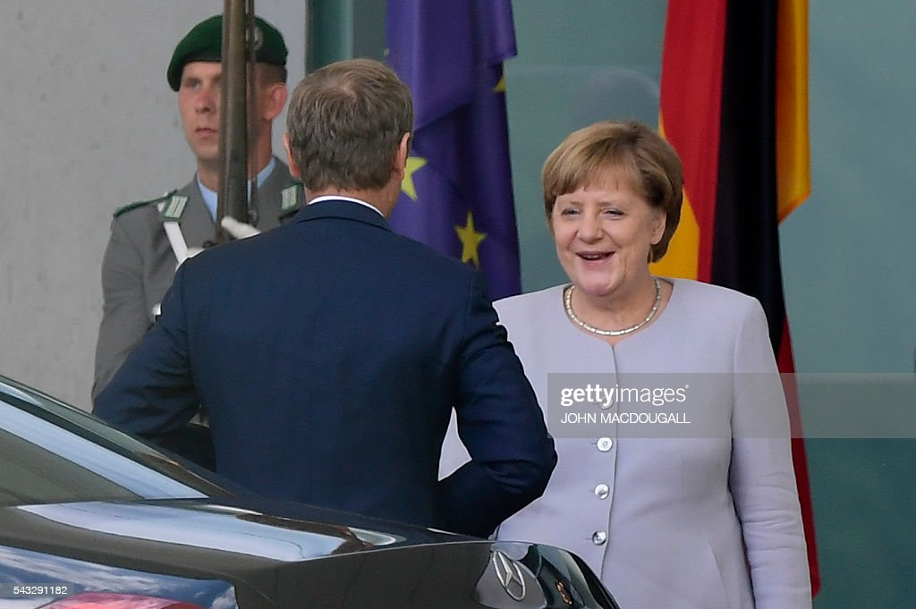 European Council president Donald Tusk (L) is welcomed by German chancellor Angela Merkel upon arrival for talks after the Brexit referendum at the chancellery in Berlin, on June 27, 2016. / AFP / John MACDOUGALL