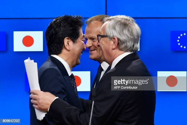 European Council President Donald Tusk Japanese Prime Minister Shinzo Abe and European Commission President JeanClaude Juncker speak as they give a...