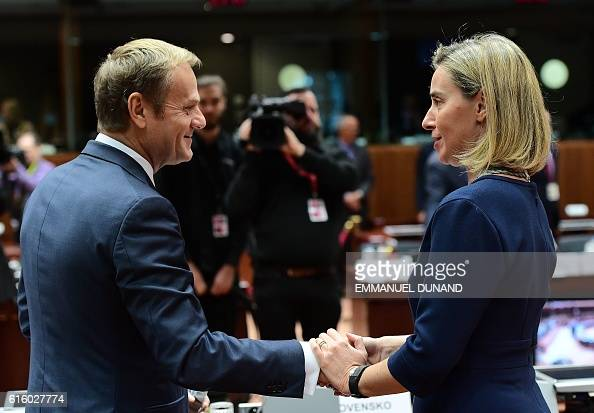European Council President Donald Tusk speaks and shakes hands with EU's High representative for foreign affairs and security policy Federica...